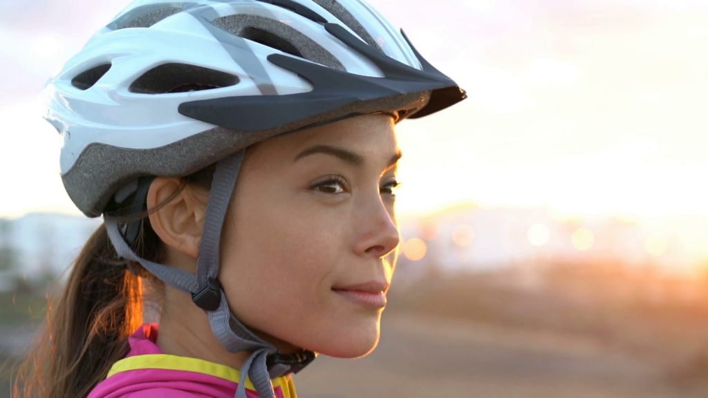 young-female-cyclist-wearing-bike-helmet-looking-at-view-during-sunset-beautiful-woman-with-cycling-helmet-enjoying-nature-while-relaxing-after-biking_