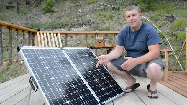 man standing next to the portable solar panel