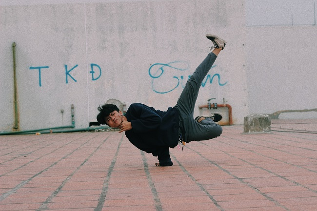picture of a boy dancing on a red concrete floor and white wall with graffiti wearing black shirt, gray pants and dancing sneakers
