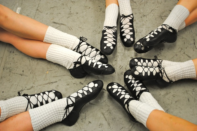 picture of girls legs in socks and black dancing shoes on a gray background
