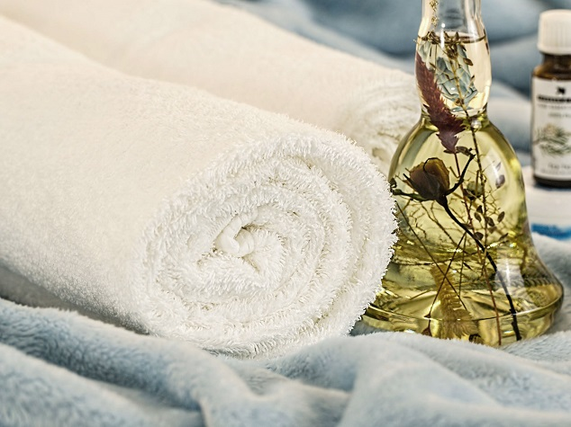 white bath towels and essential oil