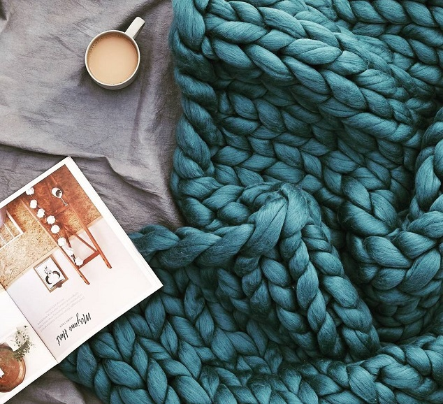 Blue merino wool blanket with a book and a cup of coffee on a bed
