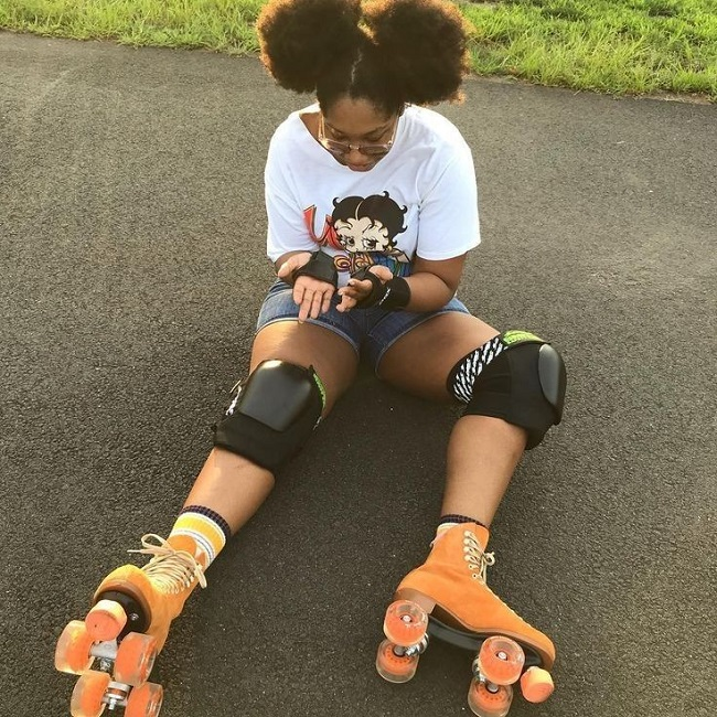picture of a girl sitting on the road wearing roller skates and protective gear